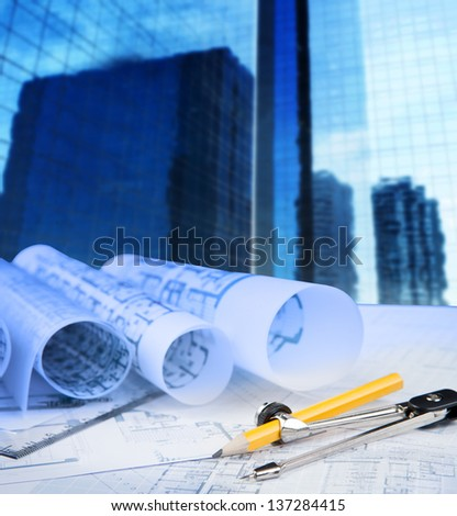 compass pencil blue print and office building in background use for construction theme - stock photo