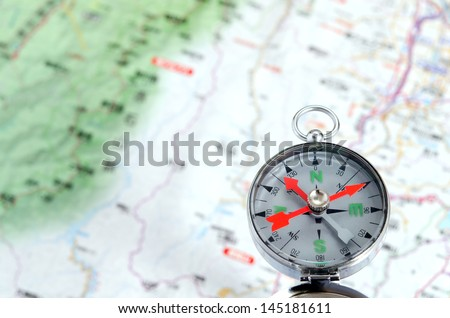Compass photoed against the background of the map - stock photo
