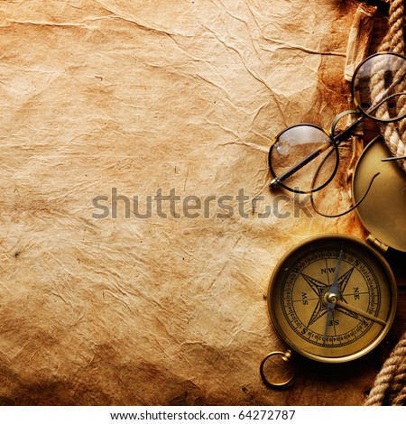 Compass, rope and glasses on old paper - stock photo