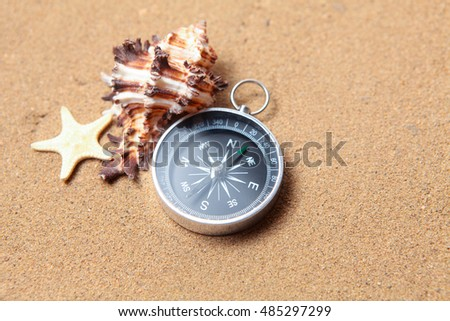 Compass, seashell on and starfish the sea sand and place for text