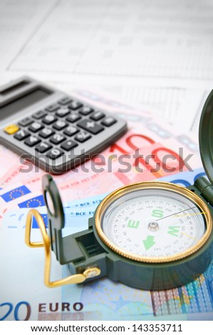 Compass, the calculator and money on documents.
