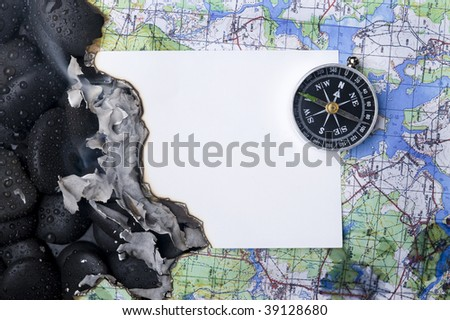 Compass with rock cover water and map - stock photo