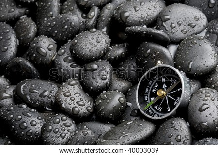 Compass with rock cover water drop - stock photo