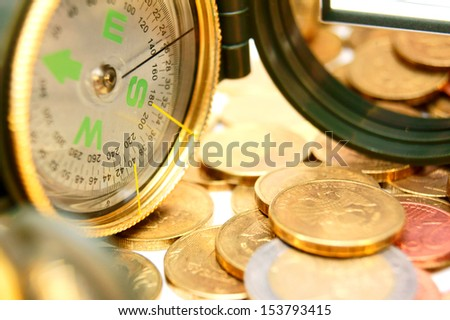 Compasses and gold coins. - stock photo