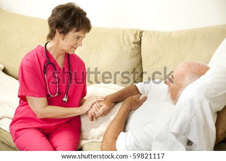 Compassionate home health nurse holds an elderly patient's hand. - stock photo
