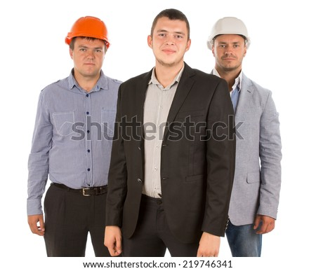 Competent happy construction team led by a young man in a suit flanked by two men in hardhats grouped together smiling at the camera, isolated on white