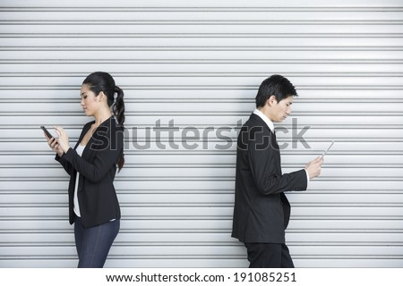 Competing with Technology: Two Chinese business colleagues ignoring each other and using portable tech device's . - stock photo