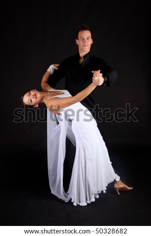 Competition ballroom dancers in formal black and white costumes against black background