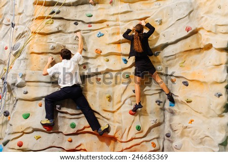 Competition between business partners on man-made cliff in the sport centre - stock photo
