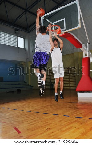 competition concept with people who playing basketball in school gym - stock photo