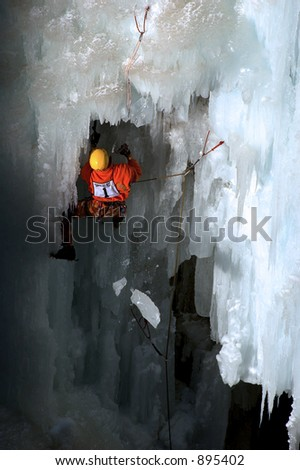 competition ice climber on route having pulled off a large chunk of ice - stock photo