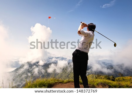 Competition in business concept: Young asian businessman hit golf ball to flag on the cloud in the sky