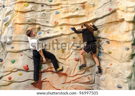 competition of young businesswoman and businessman on rock wall in sport center - stock photo