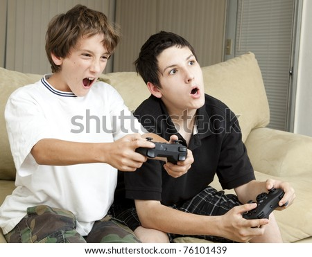 Competitive brothers playing video games at home. - stock photo