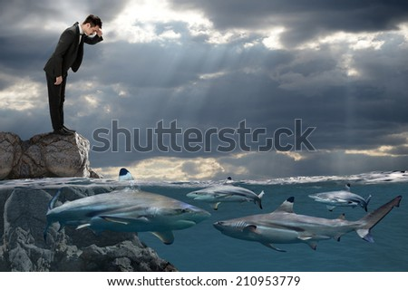 Competitive business concept with businessman looking at sharks swimming in ocean - stock photo