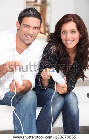 Competitive couple playing video games - stock photo