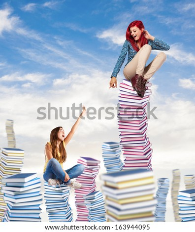 competitive young woman sitting on a books pile ascending to the sky - stock photo