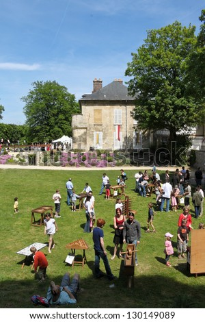 COMPIEGNE, FRANCE - MAY 22: People enjoy playing with medieval wooden toys on a fair held during annual Joan of Arc festival  on May 22, 2010 in Compiegne, France. - stock photo