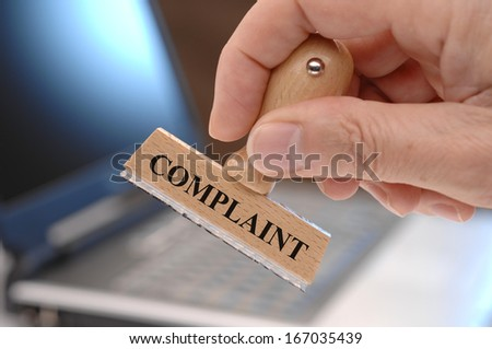 complaint marked on rubber stamp in hand - stock photo