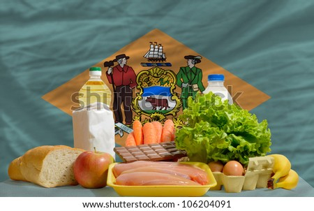 complete american state flag of delaware covers whole frame, waved, crunched and very natural looking. In front plan are fundamental food ingredients for consumers, symbolizing consumerism - stock photo