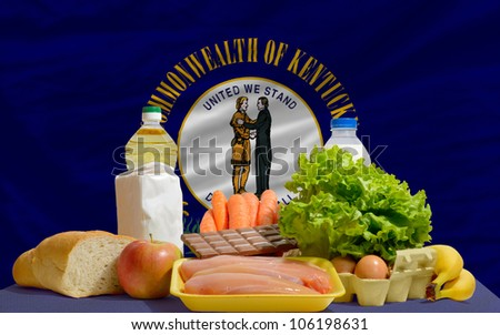 complete american state flag of kentucky covers whole frame, waved, crunched and very natural looking. In front plan are fundamental food ingredients for consumers, symbolizing consumerism - stock photo
