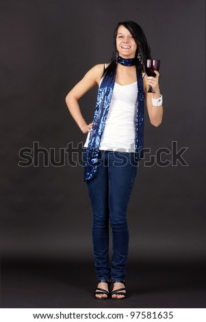 Complete body shot of a pretty young woman partying,  holding purple glass and toasting. - stock photo