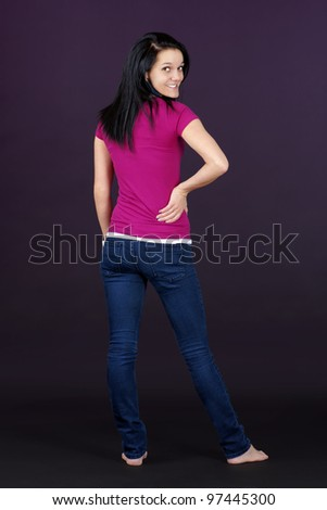 Complete body shot of casual thin and healthy pretty brunette turning around to look at camera - stock photo