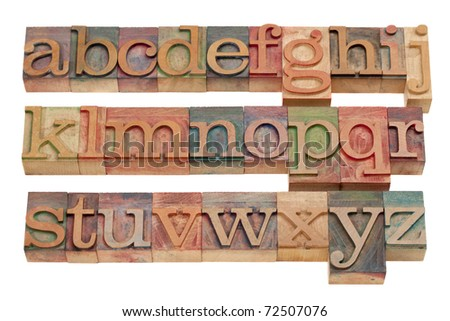 complete English alphabet (lowercase) in vintage wooden letterpress printing blocks stained by color inks, isolated on white - stock photo