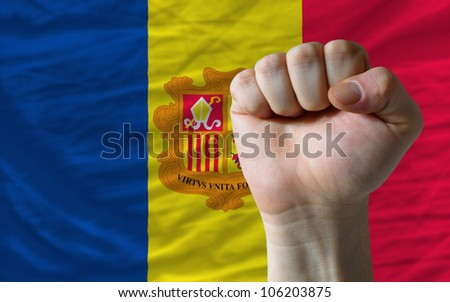 complete national flag of andorra covers whole frame, waved, crunched and very natural looking. In front plan is clenched fist symbolizing determination - stock photo