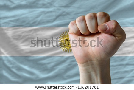 complete national flag of argentina covers whole frame, waved, crunched and very natural looking. In front plan is clenched fist symbolizing determination - stock photo