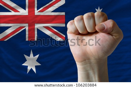 complete national flag of australia covers whole frame, waved, crunched and very natural looking. In front plan is clenched fist symbolizing determination