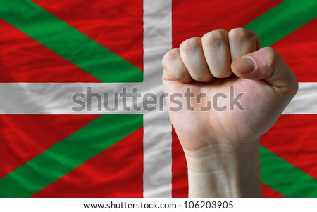 complete national flag of basque covers whole frame, waved, crunched and very natural looking. In front plan is clenched fist symbolizing determination - stock photo