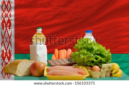 complete national flag of belarus  covers whole frame, waved, crunched and very natural looking. In front plan are fundamental food ingredients for consumers, symbolizing consumerism an human needs - stock photo