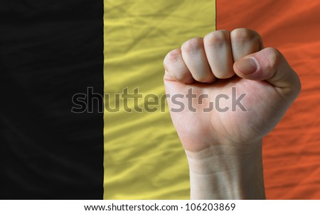 complete national flag of belgium covers whole frame, waved, crunched and very natural looking. In front plan is clenched fist symbolizing determination - stock photo