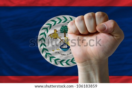complete national flag of belize covers whole frame, waved, crunched and very natural looking. In front plan is clenched fist symbolizing determination - stock photo