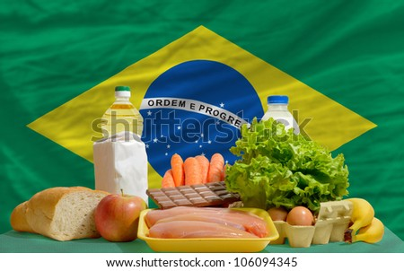 complete national flag of brazil covers whole frame, waved, crunched and very natural looking. In front plan are fundamental food ingredients for consumers, symbolizing consumerism an human needs - stock photo