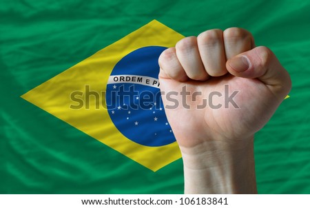 complete national flag of brazil covers whole frame, waved, crunched and very natural looking. In front plan is clenched fist symbolizing determination