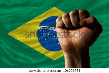 complete national flag of brazil covers whole frame, waved, crunched and very natural looking. In front plan is clenched fist symbolizing determination - stock photo