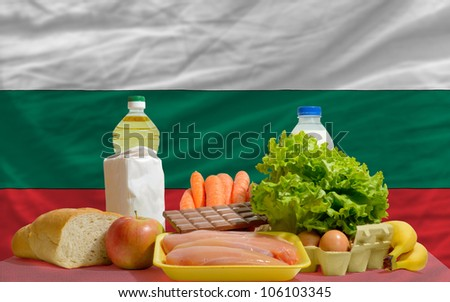 complete national flag of bulgaria covers whole frame, waved, crunched and very natural looking. In front plan are fundamental food ingredients for consumers, symbolizing consumerism an human needs - stock photo