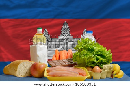 complete national flag of cambodia covers whole frame, waved, crunched and very natural looking. In front plan are fundamental food ingredients for consumers, symbolizing consumerism an human needs - stock photo