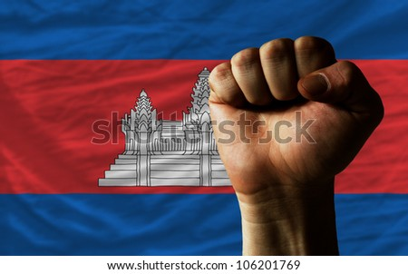 complete national flag of cambodia covers whole frame, waved, crunched and very natural looking. In front plan is clenched fist symbolizing determination - stock photo