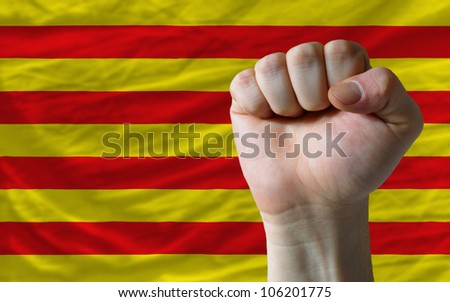 complete national flag of catalonia covers whole frame, waved, crunched and very natural looking. In front plan is clenched fist symbolizing determination - stock photo
