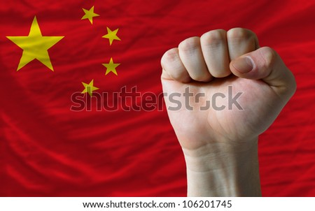 complete national flag of china covers whole frame, waved, crunched and very natural looking. In front plan is clenched fist symbolizing determination - stock photo
