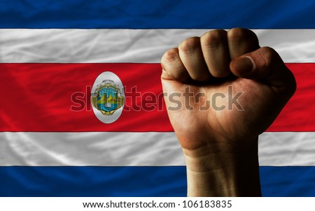 complete national flag of costarica covers whole frame, waved, crunched and very natural looking. In front plan is clenched fist symbolizing determination - stock photo