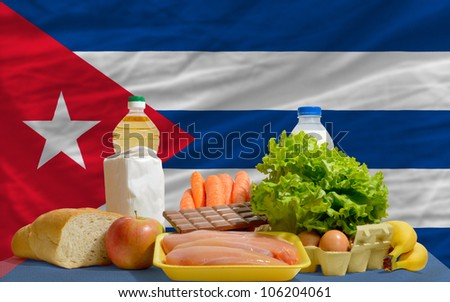 complete national flag of cuba covers whole frame, waved, crunched and very natural looking. In front plan are fundamental food ingredients for consumers, symbolizing consumerism - stock photo