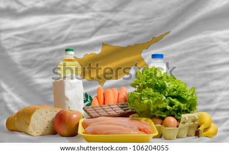 complete national flag of cyprus covers whole frame, waved, crunched and very natural looking. In front plan are fundamental food ingredients for consumers, symbolizing consumerism - stock photo