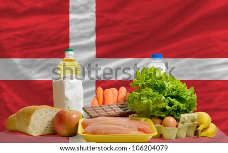 complete national flag of denmark covers whole frame, waved, crunched and very natural looking. In front plan are fundamental food ingredients for consumers, symbolizing consumerism - stock photo