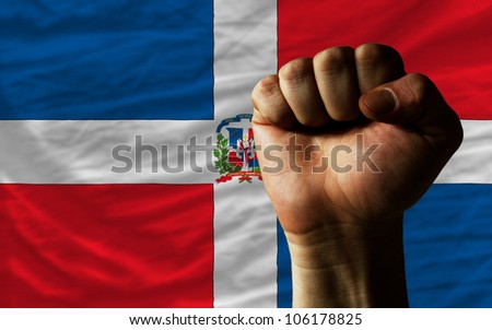 complete national flag of dominican covers whole frame, waved, crunched and very natural looking. In front plan is clenched fist symbolizing determination - stock photo