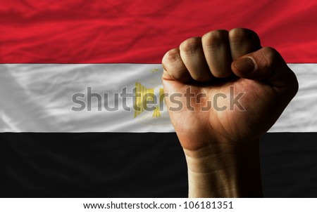 complete national flag of egypt covers whole frame, waved, crunched and very natural looking. In front plan is clenched fist symbolizing determination - stock photo