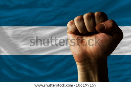 complete national flag of el salvador covers whole frame, waved, crunched and very natural looking. In front plan is clenched fist symbolizing determination - stock photo